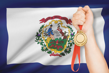 Medal in hand with flag on background - State of West Virginia.