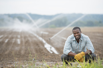 An organic vegetable farm, with water sprinklers irrigating the fields. A man in working clothes.