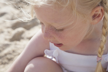 A young girl with blonde hair in pigtails on the beach.