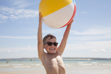 A boy wearing sunglasses on the beach. Holding an inflatable beach ball above his head.