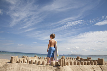 A boy standing beside a sandcastle, on top of a mound of sand. Beach.
