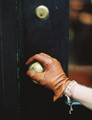 A person wearing a leather glove, opening a door.