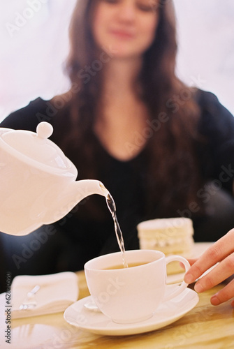 A woman pouring a cup of tea