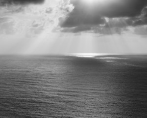 Shafts of sunlight shining through cloud and a view over the Pacific Ocean, at Manzanita, Oregon.