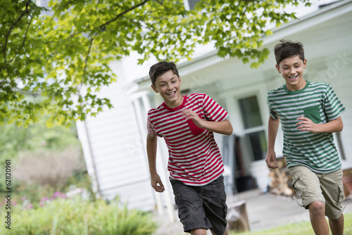 Two boys in a farmhouse garden in summer.