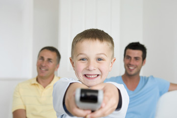 A child, a boy holding a television remote control. Two men on the sofa behind him.