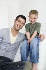 A man on a sofa beside a young boy wearing jeans.