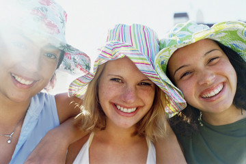 Three young girls in a row wearing sunhats looking at the camera and smiling.