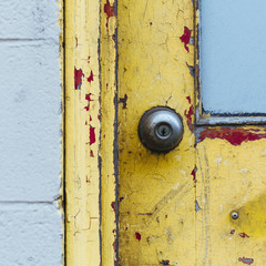 A doorway and the doorbell of a building. Flaked damaged paint.