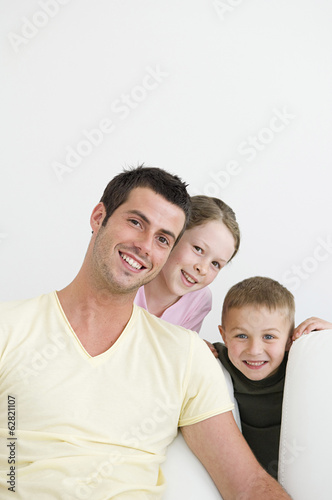 A man and two children at home, a boy and a girl.