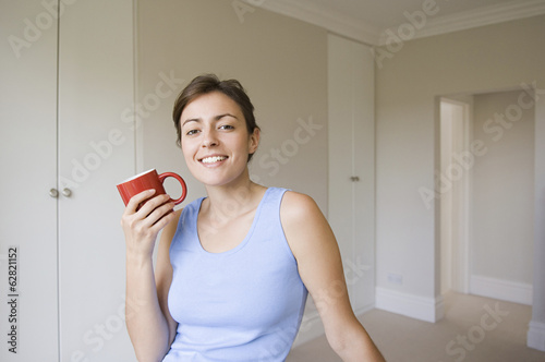 A woman wearing a blue top, seated holding a red china mug.