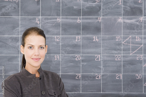 A young woman in front of a blackboard marked out as a calendar.