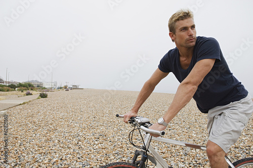 A man riding a bicycle on a shingle beach.