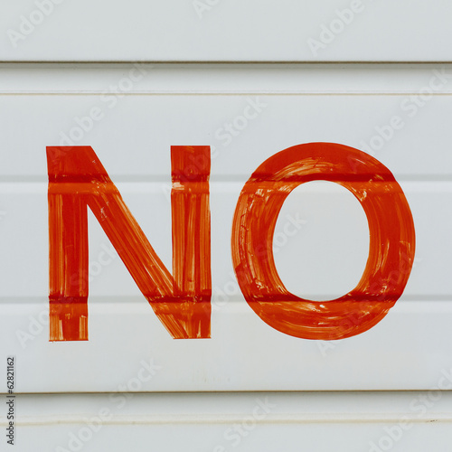 A large NO sign in red paint on a garage door, indicating No Parking.