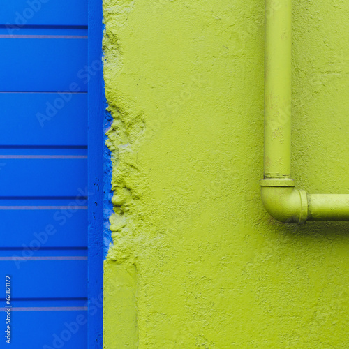 A green painted wall and pipe by a blue doorway.