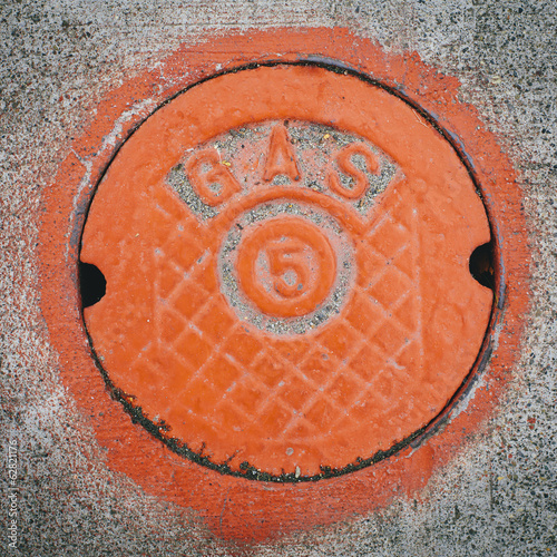 A gas manhole cover, round and painted orange on the road in Seattle.