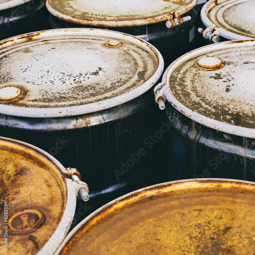 A group of rusted corroded barrels of chemical or petroleum products.