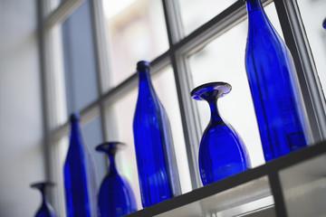 A cafe interior. Bright blue glassware on empty tables.