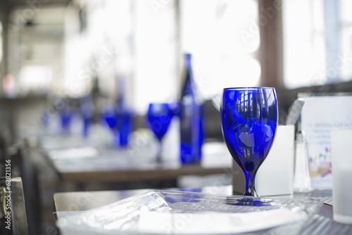A cafe interior. Bright blue glassware on empty tables.