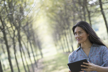 A woman standing in an avenue of trees, holding a digital tablet.