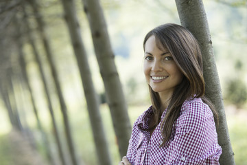 A woman standing in an avenue of trees, smiling.