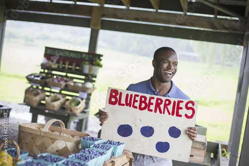 An organic fruit and vegetable farm. A  person carrying a blueberries sign.