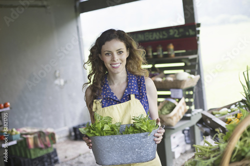 An organic farm stand. A woman sorting vegetables.