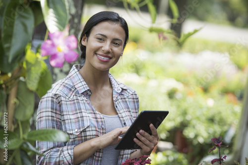 A woman in an organic nursery greenhouse, using a digital tablet.