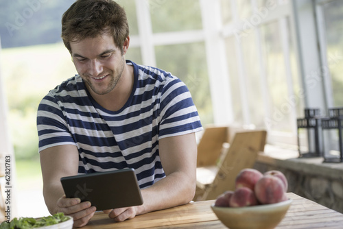 A man sitting at a table using a digital tablet.