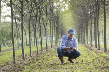 A man crouching and examining a handful of soil.