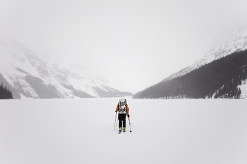 A skier crossing a frozen lake on the Wapta Traverse, a mountain hut-to-hut ski tour in Alberta, Canada.