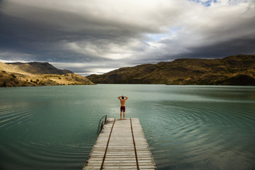 A young man standing at the end of a wooden pier, preparing to dive into calm lake surrounded by mountains in Torres del Paine National Park, Chile.