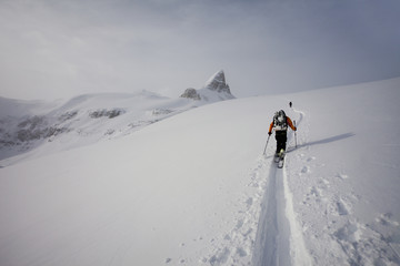 Two skiers ascending a ridge in mist and cloud conditions on the Wapta Traverse, a mountain hut to hut ski tour in Alberta, Canada.