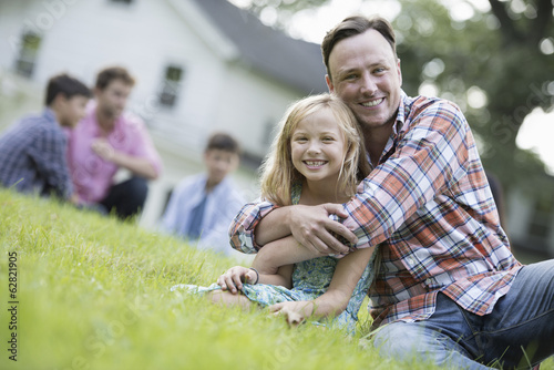 A father and daughter at a summer party, sitting on the grass.