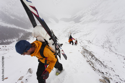 Three skiers ascending a ridge in mist and cloud conditions on the Wapta Traverse, a mountain hut-to-hut ski tour in Alberta, Canada.