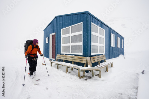 A skier leaving a refuge hut in mist and cloud conditions on the Wapta Traverse, a mountain hut to hut ski tour in Alberta, Canada.