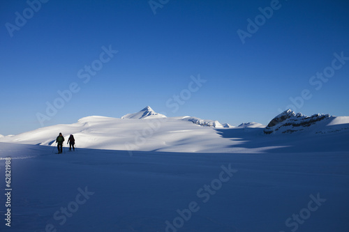 Two skiers on a slope taking in the view of the mountainous landscape of the Wapta Traverse in the Rocky Mountains.