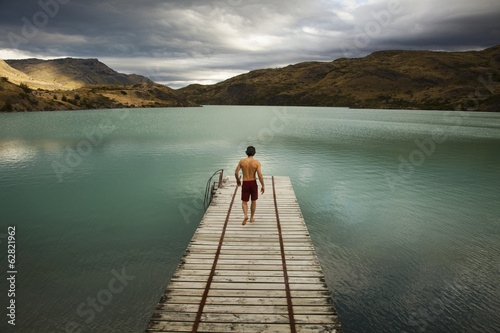 A young man walking down a wooden pier, towards calm lake surrounded by mountains in Torres del Paine National Park, Chile.