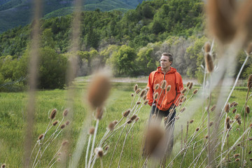 A man in an orange jacket walking his property.