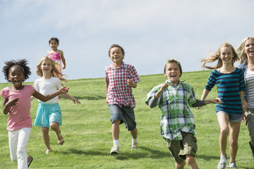A group of children running across a grass field.