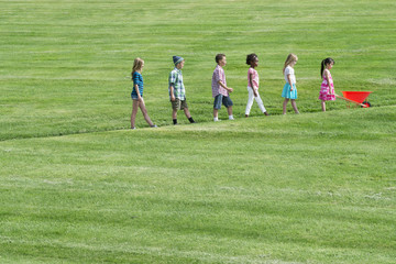 A group of children walking up a sloping path in height order following the smallest one at the front with a red wheelbarrow.