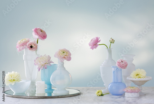 A group of containers, jugs and vases with a variety of pastel coloured delicate flowers. Studio shot.