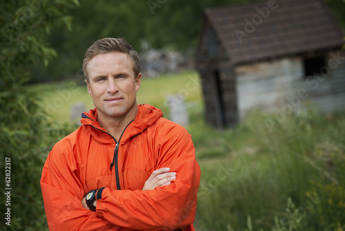 A young man with his arms folded in a bright orange jacket.