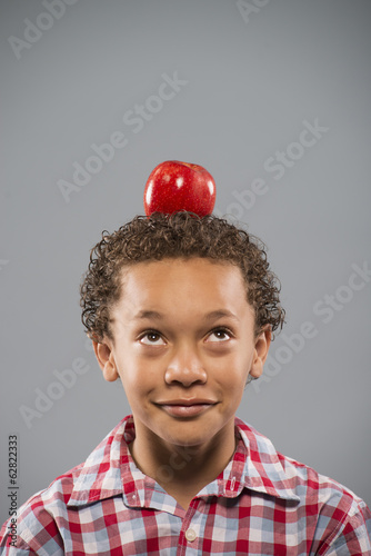 A boy concentrating on sitting still with a large red apple balanced on his head.