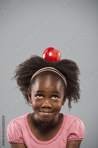 A girl concentrating on sitting still with a large red apple balanced on her head.