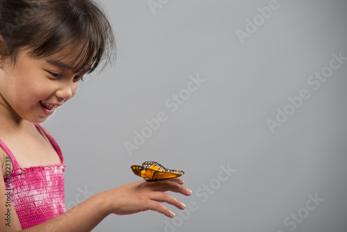 A child with a butterfly on her hand, keeping very still.