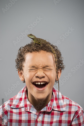 A boy with a lizard with a long tail crawling on top of his head.