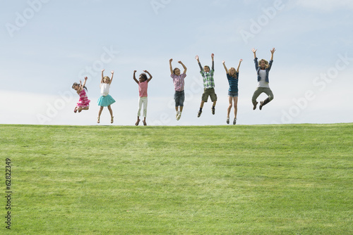 A group of children on the top of a hill, in a row leaping into the air.