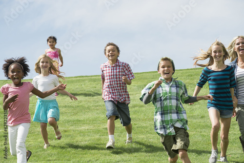 A group of children running across a grass field.