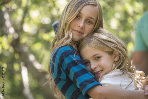 A group of children and adults in the shade of trees in woodland. Friends and family outdoors together.